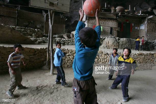Chinese children play basketball in the playground of a school in a huge cave at a remote Miao village on March 16 2007 in Ziyun county Guizhou...