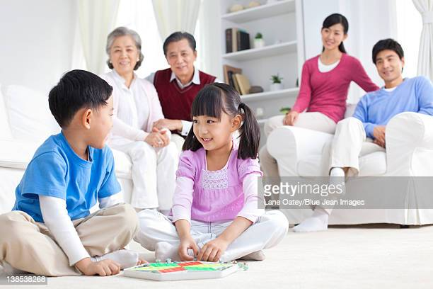 Chinese children playing with toys on the floor with grandparents and parents behind them