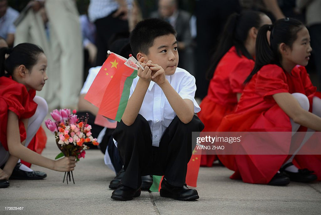 Chinese children rest as they wait for the arrival of Belarusian President Alexander Lukashenko and Chinese President Xi Jinping during a welcoming...