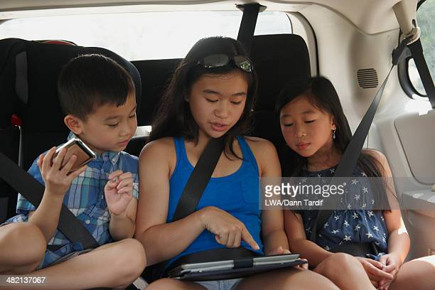 Chinese children using digital tablet in backseat of car