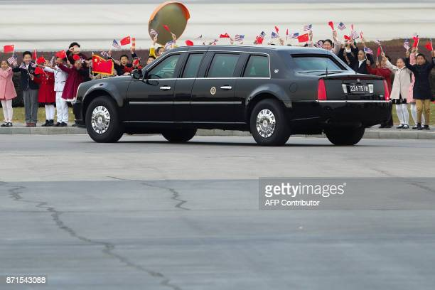 Chinese children wave to the car carrying US President Donald Trump and First Lady Melania Trump after their arrival at Beijing Capital Airport on...