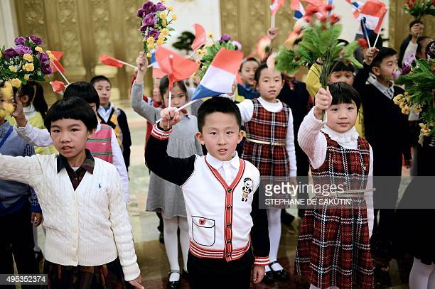 Chinese children waving French flags and flowers wait before the official ceremony with China's President Xi Jinping and French President Francois...