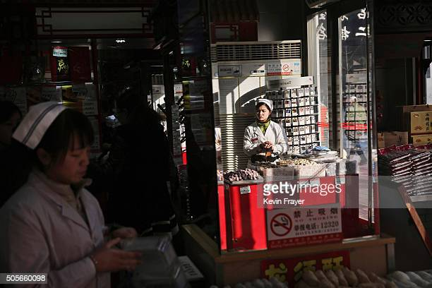 Chinese clerks wait for customers at a department storet on January 19 2016 in Beijing China In 2015 China's economy grew at its slowest rate in a...