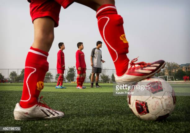 Chinese coach interacts students during training on the at the Evergrande International Football School on June 14 2014 near Qingyuan in Guangdong...