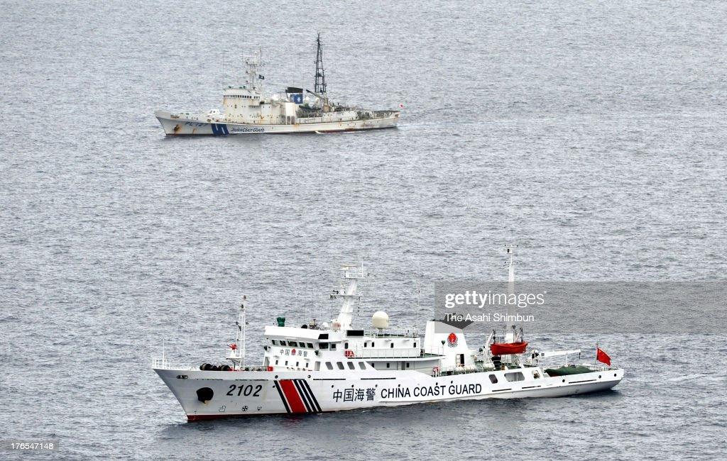 A Chinese Coast Guard vessel cruises with Japan Coast Guard patrol ship at the contiguous zone near disputed Senkaku Island on the day Japan marks...