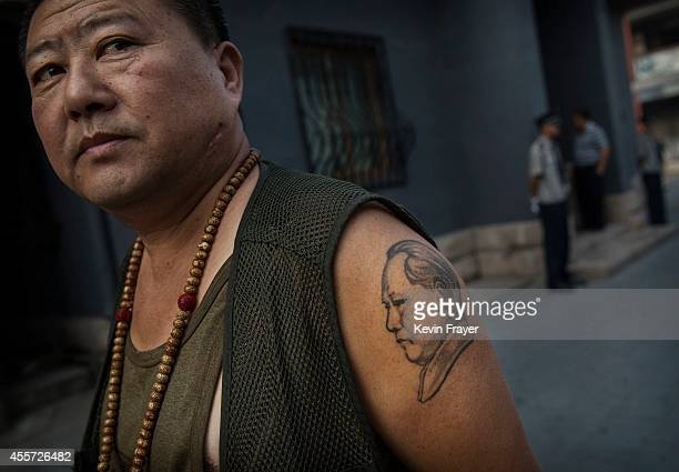 Chinese collector has a tattoo of the late Mao Zedong on his arm as he waits outside a sale and auction of memorabilia dedicated to him on September...