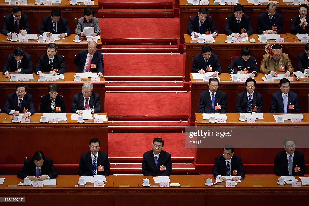 Chinese Communist Party General Secretary and incoming-President Xi Jinping (Below Center), incoming-Chairman of the Standing Committee of the National People's Congress Zhang Dejiang (Below 2nd Left), incoming-Premier Li Keqiang (Below 2nd Right) and incoming-Chairman of Chinese People's Political Consultative Conference Yu Zhengsheng (Right) attend a plenary session of the National People's Congress at the Great Hall of the People on March 10, 2013 in Beijing, China. The State Council, China's cabinet, will begin its seventh restructuring attempt in the past three decades to roll back red tape and reduce administrative intervention. Several departments under the State Council will be reorganized according to a plan on the institutional restructuring and functional transformation of the State Council, which was submitted to the plenary session of the National People's Congress Sunday.