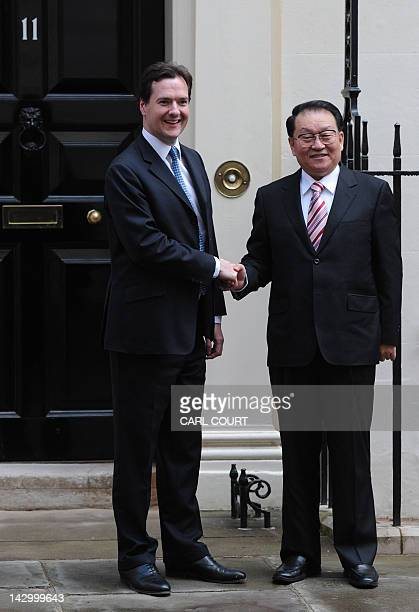 Chinese Communist Party official Li Changchun a senior member of China's Politburo Standing Committee shakes hands with British Chancellor of the...