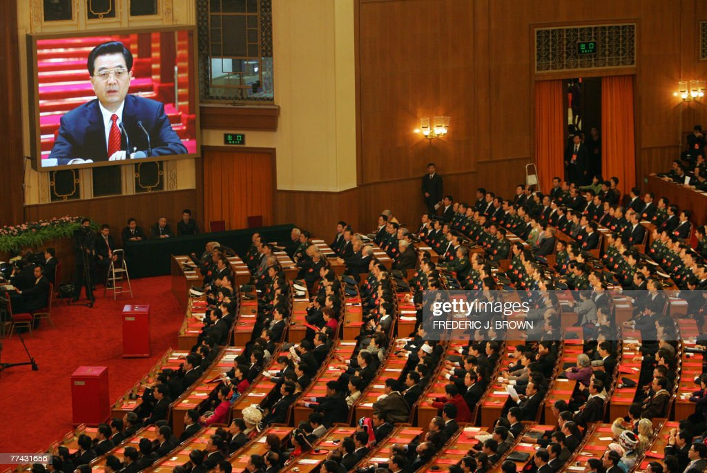 Chinese Communists wrap up their 17th five-yearly Party Congress inside the Great Hall of the People in Beijing, 21 October 2007, as President Hu Jintao is seen on a big screen addressing delegates in a live telecast. China's Communist Party ended its Congress after amending its charter to include President Hu's vision for the nation and endorsing leadership changes after Hu declared the event over in a short ceremony to mark the end of the week-long meeting that gathered more than 2,200 top cadres in Beijing. AFP PHOTO/Frederic J. BROWN