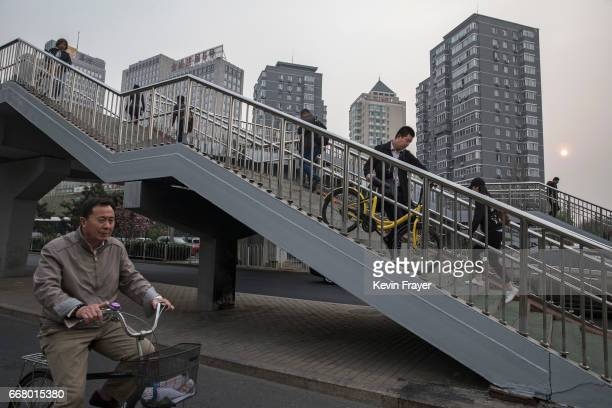 Chinese commuter carries a ride share down a footbridge on April 7 2017 in Beijing China The popularity of bike shares has exploded in the past year...
