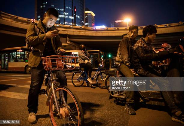 Chinese commuter checks his mobile as he sits on a bike share during rush hour on March 27 2017 in Beijing China The popularity of bike shares has...