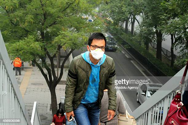 Chinese commuter is seen with a mask during a thick smoke prompted an orange alert the second highest alert which means 'be prepared' and air quality...