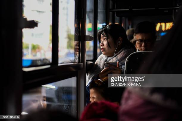 A Chinese commuter looks out of a bus window in Shanghai on December 8 2017 / AFP PHOTO / CHANDAN KHANNA
