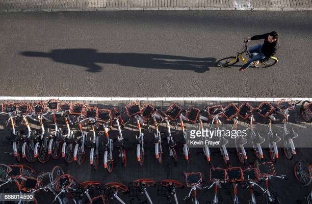 Chinese commuter rides past a large group of Mobike ride share bicycles at a distribution area during rush hour on April 11 2017 in Beijing China The...