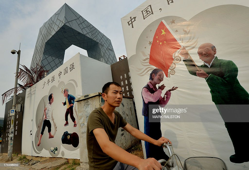 A Chinese commuter rides past 'Chinese Dream' promotion billboards beside the CCTV office tower in the Central Business District in Beijing on July 26, 2013. Decades of breakneck expansion have given China gleaming skyscrapers and sleek railways, but brought piles of debt and dubious financial instruments analysts say are a potential time bomb that could strike a blow against global growth. AFP PHOTO/Mark RALSTON