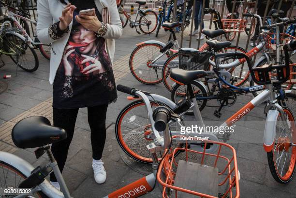 Chinese commuter uses her mobile phone to collect a Mobike bike share on April 6 2017 in Beijing China The popularity of bike shares has exploded in...