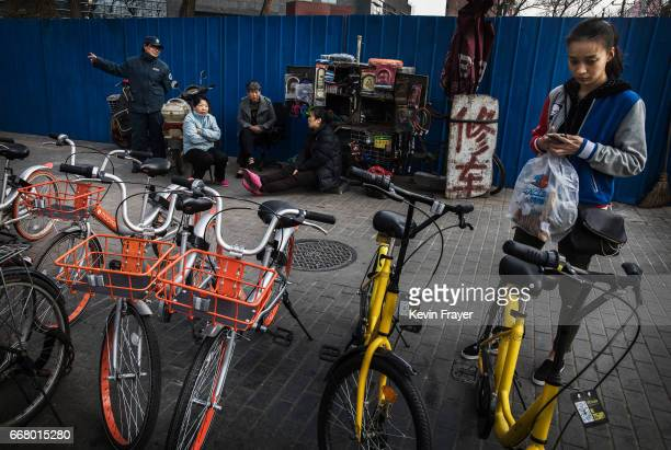 Chinese commuter uses her mobile phone to take a bike share on March 29 2017 in Beijing China The popularity of bike shares has exploded in the past...