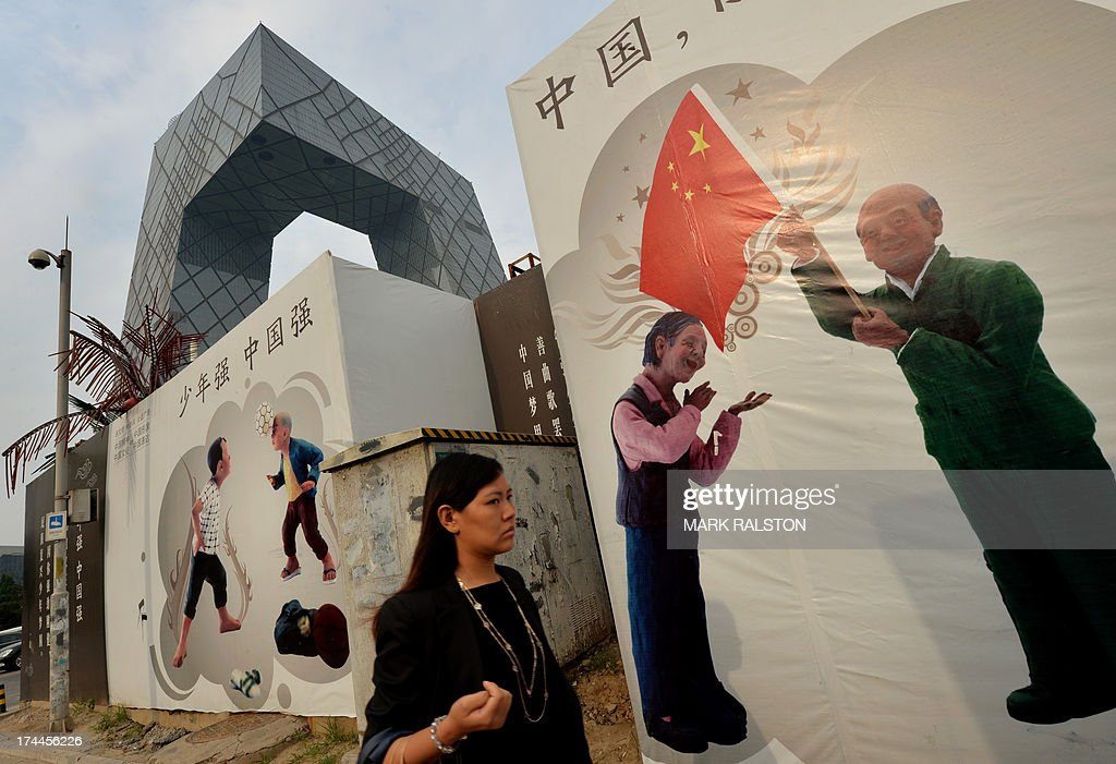A Chinese commuter walks past 'China Dream' promotion billboards beside the CCTV office tower in the Central Business District in Beijing on July 26, 2013. Decades of breakneck expansion have given China gleaming skyscrapers and sleek railways, but brought piles of debt and dubious financial instruments analysts say are a potential time bomb that could strike a blow against global growth. AFP PHOTO/Mark RALSTON