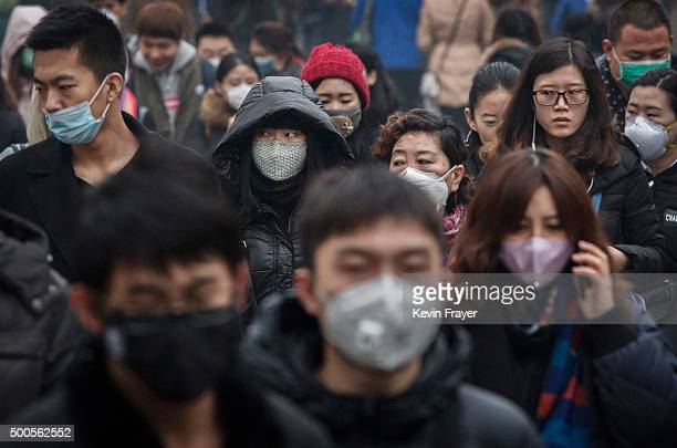 Chinese commuters many wearing masks walk to work during heavy pollution on December 9 2015 in Beijing China The Beijing government issued a 'red...