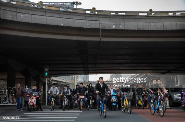 Chinese commuters most riding bike shares cross an intersection during rush hour on March 28 2017 in Beijing China The popularity of bike shares has...