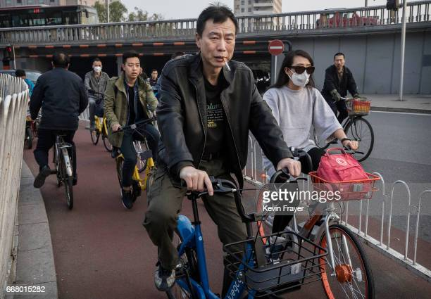 Chinese commuters ride various bike shares near a metro station on April 6 2017 in Beijing China The popularity of bike shares has exploded in the...