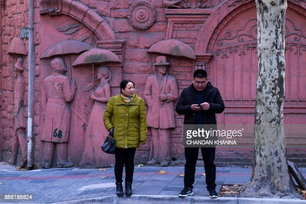Chinese commuters stand in front of a relief mural while waiting for the bus in Shanghai on December 8 2017 / AFP PHOTO / CHANDAN KHANNA