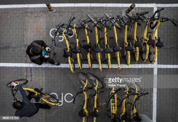 Chinese commuters take ride shares bicycles from Ofo at a distribution area during rush hour on April 11 2017 in Beijing China The popularity of bike...
