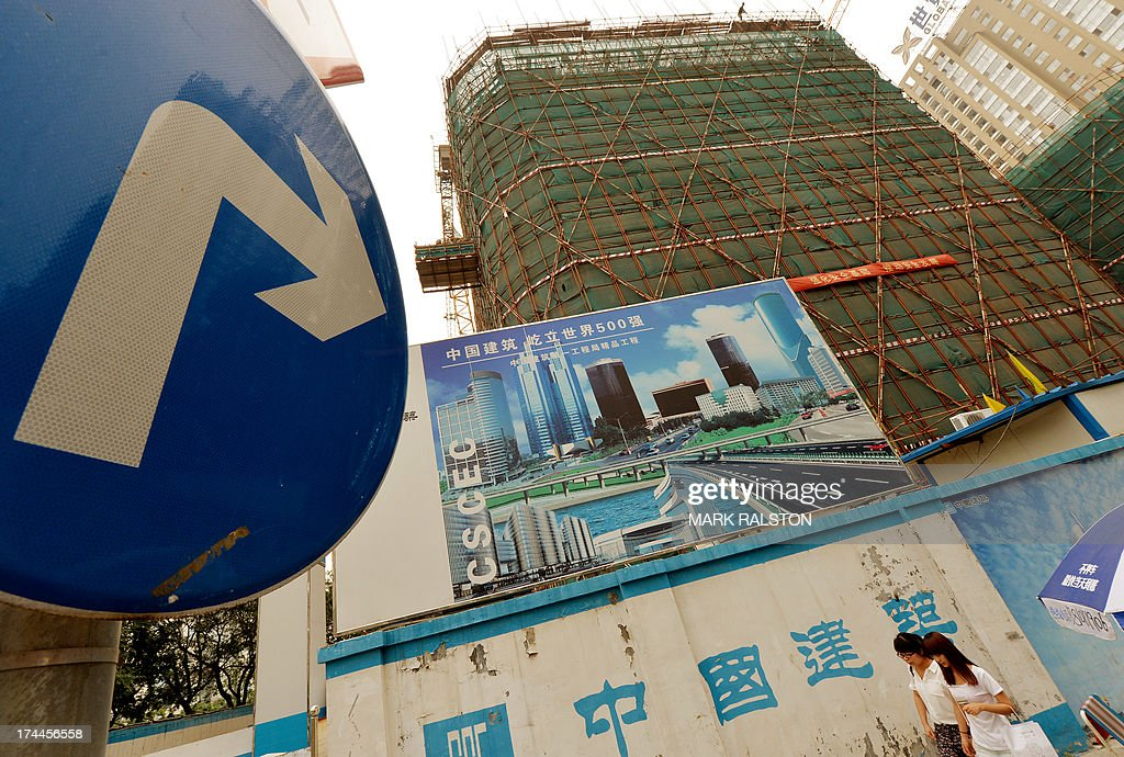 Chinese commuters walk past property development billboards in the Central Business District in Beijing on July 26, 2013. Decades of breakneck expansion have given China gleaming skyscrapers and sleek railways, but brought piles of debt and dubious financial instruments analysts say are a potential time bomb that could strike a blow against global growth. AFP PHOTO/Mark RALSTON
