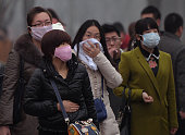 Chinese commuters wear face masks as heavy air pollution continues to shroud Beijing on February 25 2014 China's cities are often hit by heavy...