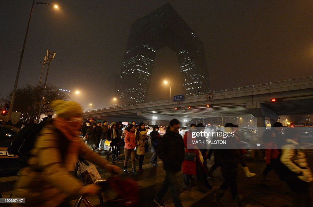Chinese commuters wear face masks as they pass by the new CCTV building during heavy air pollution in Beijing on January 30, 2013. Beijing urged residents to stay indoors as emergency measures were rolled out aimed at countering a heavy cloud of smog blanketing the Chinese capital and swathes of the country. The municipal government said children, the elderly and people sensitive to poor air quality should remain indoors, after authorities announced the closure of 103 factories and ordered 30 percent of official cars off the road. AFP PHOTO/Mark RALSTON