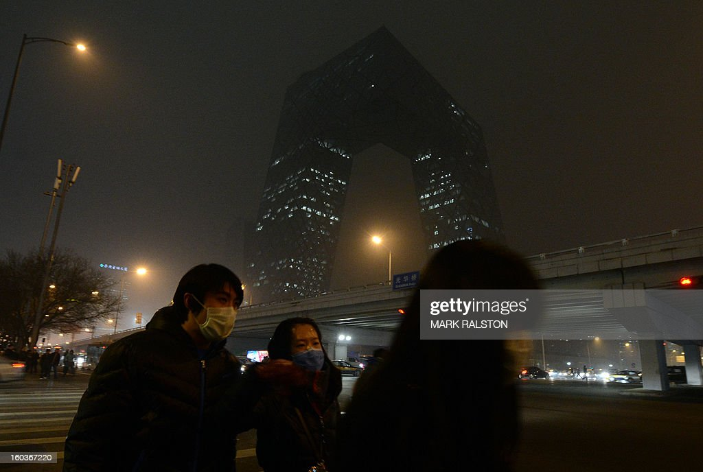 Chinese commuters wear face masks as they walk past the new CCTV building during heavy air pollution in Beijing on January 30, 2013. Beijing urged residents to stay indoors as emergency measures were rolled out aimed at countering a heavy cloud of smog blanketing the Chinese capital and swathes of the country. The municipal government said children, the elderly and people sensitive to poor air quality should remain indoors, after authorities announced the closure of 103 factories and ordered 30 percent of official cars off the road. AFP PHOTO/Mark RALSTON