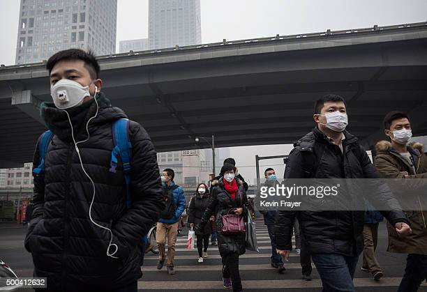 Chinese commuters wear masks to protect against pollution as they commute to work in heavy smog on December 8 2015 in Beijing China The Beijing...