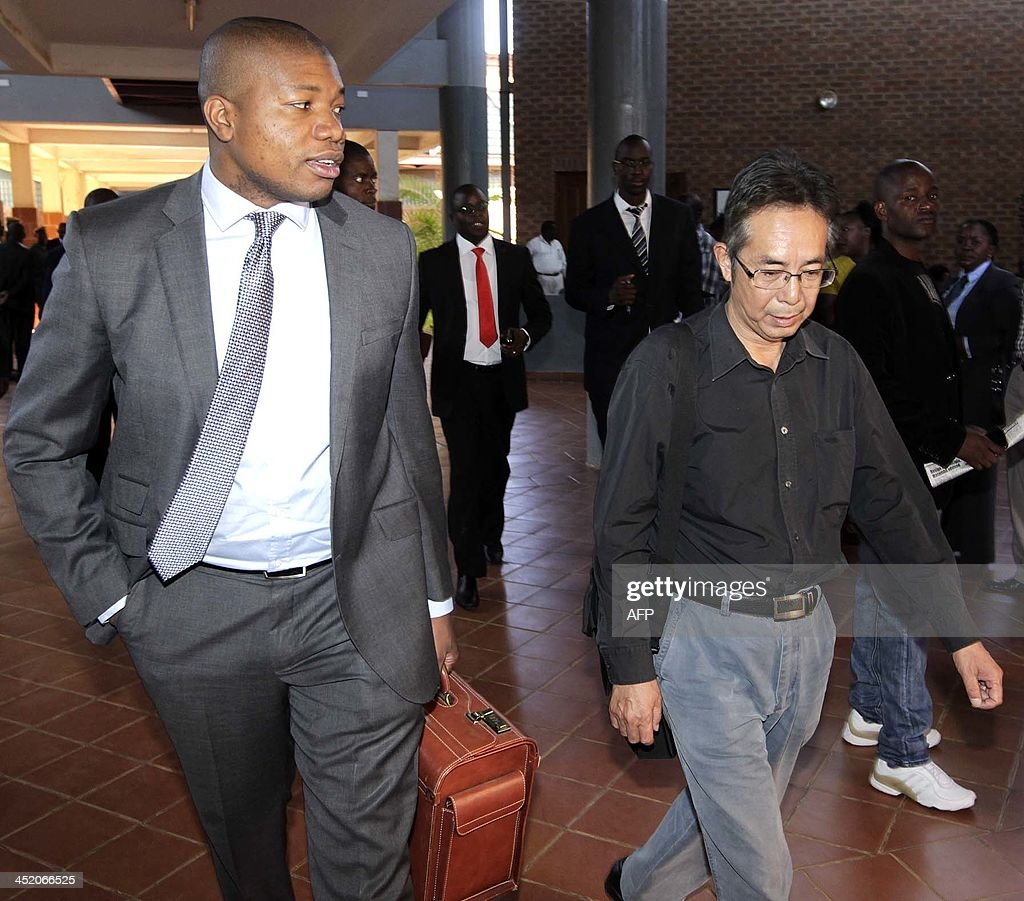 Chinese Construction and Engineering company SOGECOA's director Jack Gao arrives flanked by his lawyer Mulenga Chiteba at Lusaka's court on November...