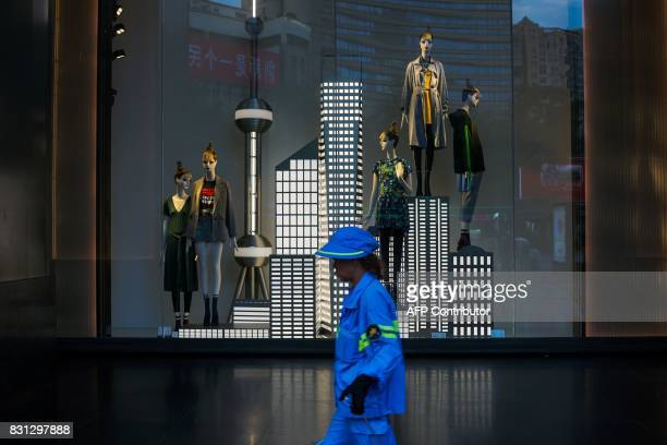 A Chinese construction woman walks past a garment store in Shanghai on August 14 2017 China's industrial output a key engine of growth slowed sharply...