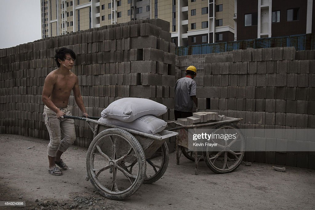 A Chinese construction worker pushes a load of concrete mix at the building site of a new apartment complex on August 29, 2014 in Beijing, China. Rapid construction and widespread over-investment in Chinese property created a bubble that continues to deflate. Prices are down, the economy has cooled and newly-constructed projects in many parts of the country remain unoccupied. The housing market accounts for more than 15% of China's annual economic output and so the softening of the market is having a broader economic impact. Analysts believe that a property collapse is unlikely though as local governments are shoring up the sector.