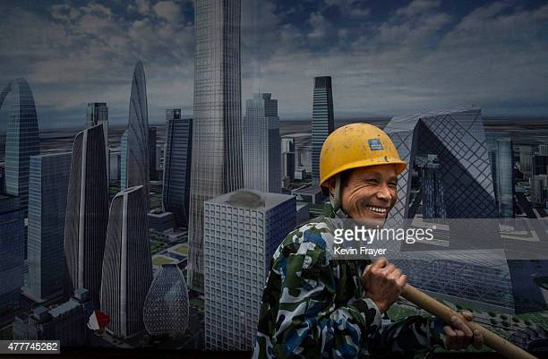 Chinese construction worker smiles towards a coworker as he walks passed a large billboard showing the the citiy's skyline on June 19 2015 in Beijing...