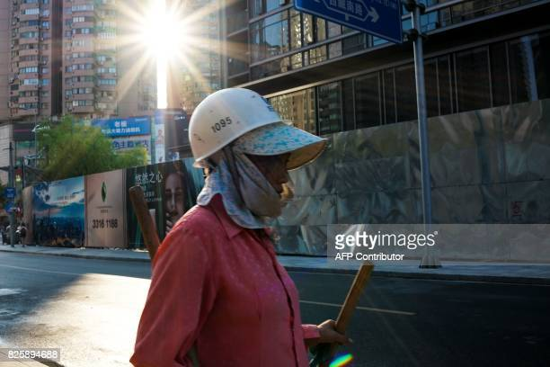 A Chinese construction worker walks on a street in Shanghai on August 3 2017 / AFP PHOTO / CHANDAN KHANNA