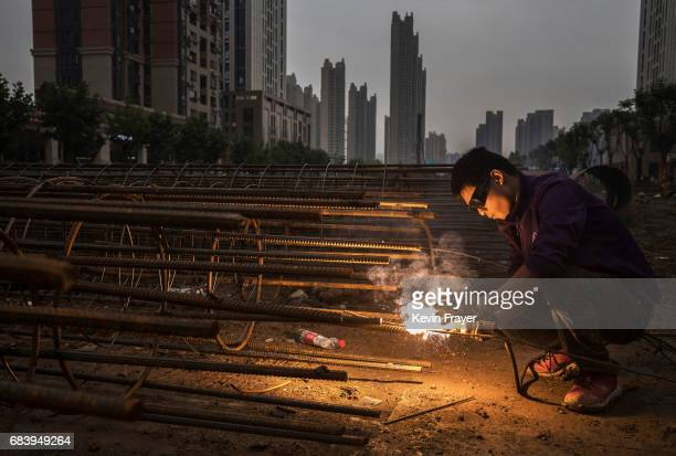 Chinese construction worker welds steel at a construction site for a new development on May 15 2017 in Wuhan Hubei province China