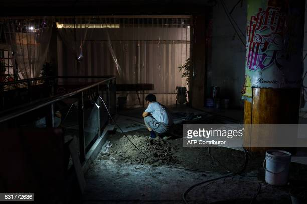 A Chinese construction worker works inside a shopping complex in Shanghai on August 15 2017 The International Monetary Fund is scheduled to release...