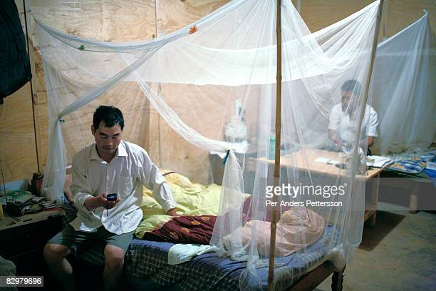 Chinese construction worker writes a SMS to his wife in China while sitting on his bed on March 27 2007 in Ndola Zambia He works for China Henan a...
