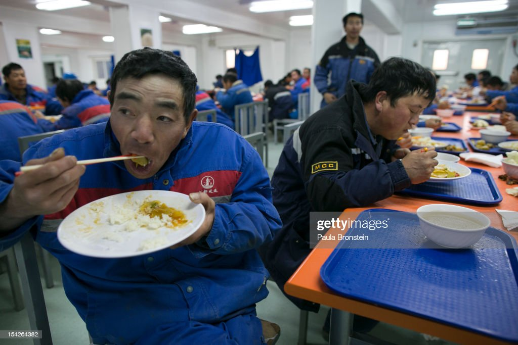 Chinese construction workers eat in the dining hall at the Chinese camp at the Oyu Tolgoi mine October 11, 2012 in the south Gobi desert, Khanbogd region, Mongolia. About 2,500 Chinese workers are contracted to help with construction onsite. The Oyu Tolgoi (Mongolian for Turquoise Hill) copper and gold mine is a combined open pit and underground mining project. The site, discovered in 2001, is located approximately 550 km south of the Mongolian capital, Ulan-Batar in the South Gobi Desert. Turquoise Hill Resources (Formerly Ivanhoe Mines) and Rio Tinto signed a long-term comprehensive investment agreement with the Government of Mongolia in 2009 with the deal awarding Turquoise Hill Resources, whose majority shareholder is Rio Tinto, with a controlling 66 percent interest and The Mongolian Government with a 34 percent interest in the project. Rio Tinto provided a comprehensive financing package and assumed direct management of the project under an agreement with Ivanhoe Mines. Initial production from open pit mining is currently underway and commercial production is planned to start in first half of 2013. An 85million USD investment was earmarked for education and training projects, with Mongolians expected to constitute 90 percent of the work force when production begins in 2013. When Oyu Tolgoi starts fully operating Mongolia will be set to become one of the world's top copper and gold producers with production estimates of 450,000 tons of copper and 330,000 ounces of gold annually. Mongolia is currently the world's fastest growing economy with its GDP increasing by more than 17 percent last year and an estimated $1.3 trillion in untapped mineral resources. Oyu Tolgoi is Mongolia's largest foreign investment project and the country's biggest economic undertaking to date, which is projected to add one-third of future value to the country's GDP by 2020.