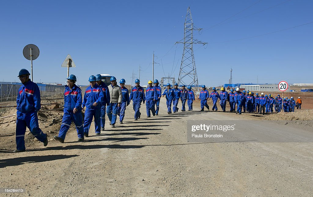 Chinese construction workers march together as they leave on a lunch break at the Oyu Tolgoi mine October 11, 2012 in the south Gobi desert, Khanbogd region, Mongolia. About 2,500 Chinese workers are contracted to help with construction onsite. The Oyu Tolgoi (Mongolian for Turquoise Hill) copper and gold mine is a combined open pit and underground mining project. The site, discovered in 2001, is located approximately 550 km south of the Mongolian capital, Ulan-Batar in the South Gobi Desert. Turquoise Hill Resources (Formerly Ivanhoe Mines) and Rio Tinto signed a long-term comprehensive investment agreement with the Government of Mongolia in 2009 with the deal awarding Turquoise Hill Resources, whose majority shareholder is Rio Tinto, with a controlling 66 percent interest and The Mongolian Government with a 34 percent interest in the project. Rio Tinto provided a comprehensive financing package and assumed direct management of the project under an agreement with Ivanhoe Mines. Initial production from open pit mining is currently underway and commercial production is planned to start in first half of 2013. An 85million USD investment was earmarked for education and training projects, with Mongolians expected to constitute 90 percent of the work force when production begins in 2013. When Oyu Tolgoi starts fully operating Mongolia will be set to become one of the world's top copper and gold producers with production estimates of 450,000 tons of copper and 330,000 ounces of gold annually. Mongolia is currently the world's fastest growing economy with its GDP increasing by more than 17 percent last year and an estimated $1.3 trillion in untapped mineral resources. Oyu Tolgoi is Mongolia's largest foreign investment project and the country's biggest economic undertaking to date, which is projected to add one-third of future value to the country's GDP by 2020.