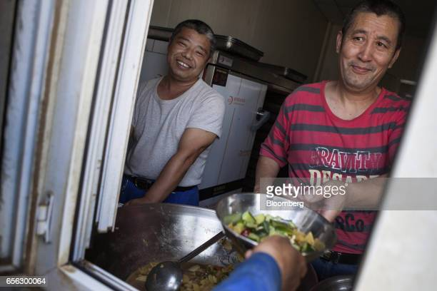 A Chinese cook hands over food to a worker during a break at the Sindh Engro Coal Mining Co site in the Thar desert Pakistan on Thursday March 9 2017...