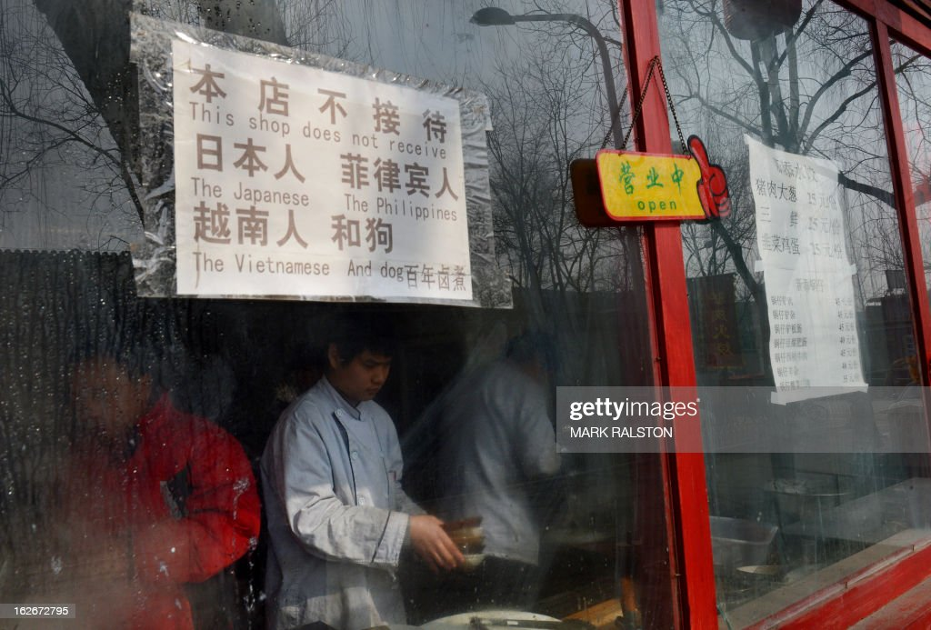 A Chinese cook works in a restaurant behind a sign that says 'This shop does not receive the Japanese, The Philippines, The Vietnamese and Dog' at the historic tourist district of Houhai in Beijing on February 26, 2013. China is currently in border disputes with Japan, Vietnam and the Philippines and has grown increasingly assertive in recent years in claiming islands and waters even without effective control of them -- in some cases hundreds of kilometres from the Chinese mainland and close to rival claimants' coasts. AFP PHOTO/Mark RALSTON