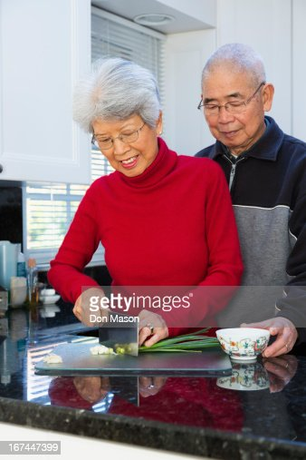 Chinese couple chopping onions in kitchen : Stock Photo