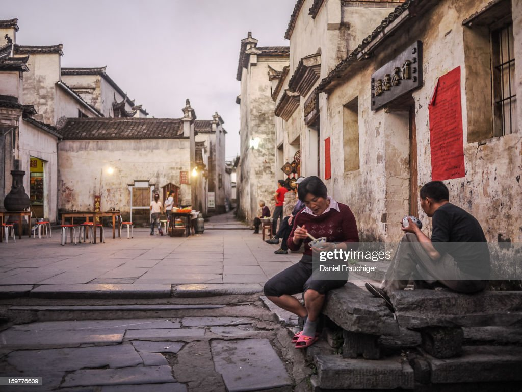 CONTENT] Chinese couple eating dinner on Xidi market square. In Xidi, Anhui, China. September 28, 2011.