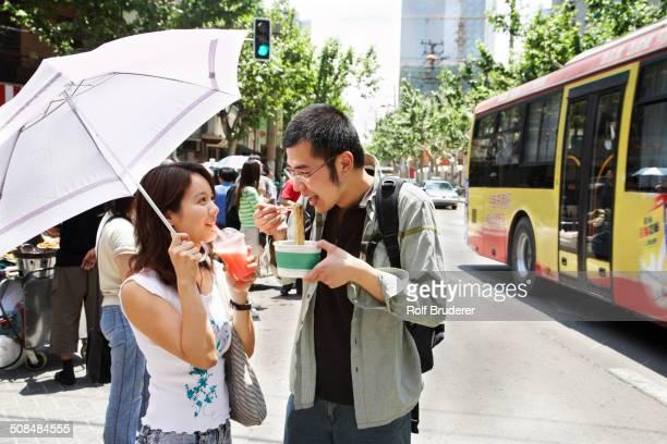 Chinese couple eating on city street, Shanghai, China