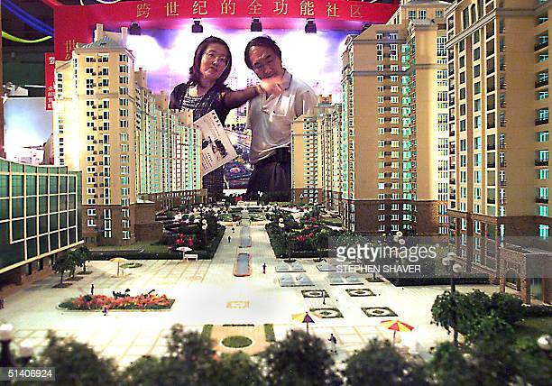 Chinese couple look at a giant model of a new upscale housing estate on display at a real estate exhibition 14 July 1999 in Beijing Local governments...