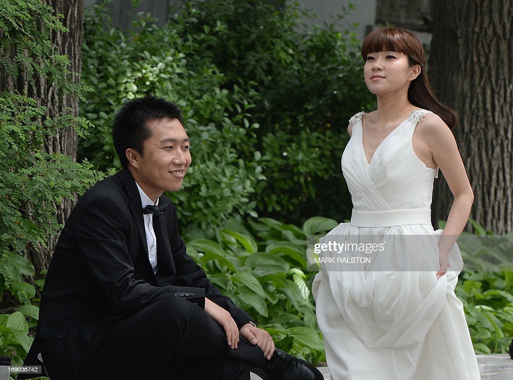 A Chinese couple poses for their wedding photos at Houhai Lake in Beijing on May 19, 2013. Beijing's parks and lakes provide a colourful backdrop for wedding photos during the spring weather, with some couples taking their photos six months before the actual wedding. AFP PHOTO / Mark RALSTON