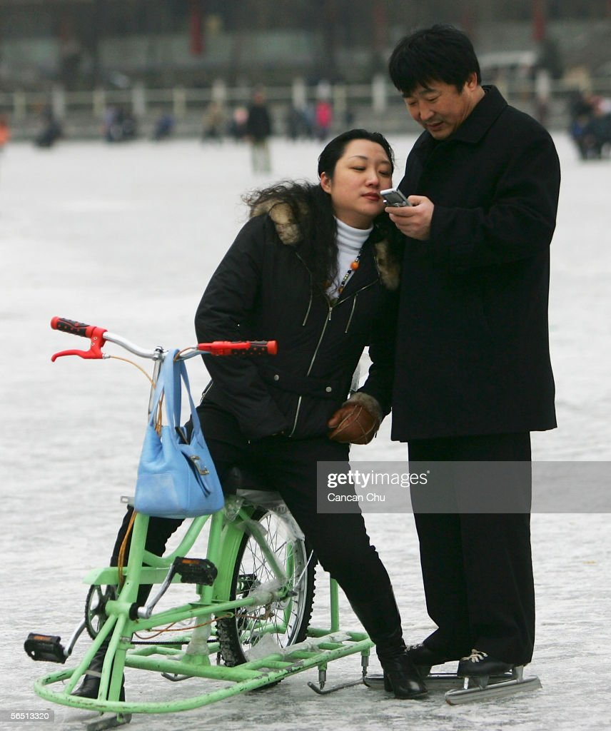 A Chinese couple read a text message on a mobile phone on the frozen Shichahai Lake on January 3, 2006 in Beijing, China. Shichahai Lake is a popular place for winter sport and entertainment in Beijing.